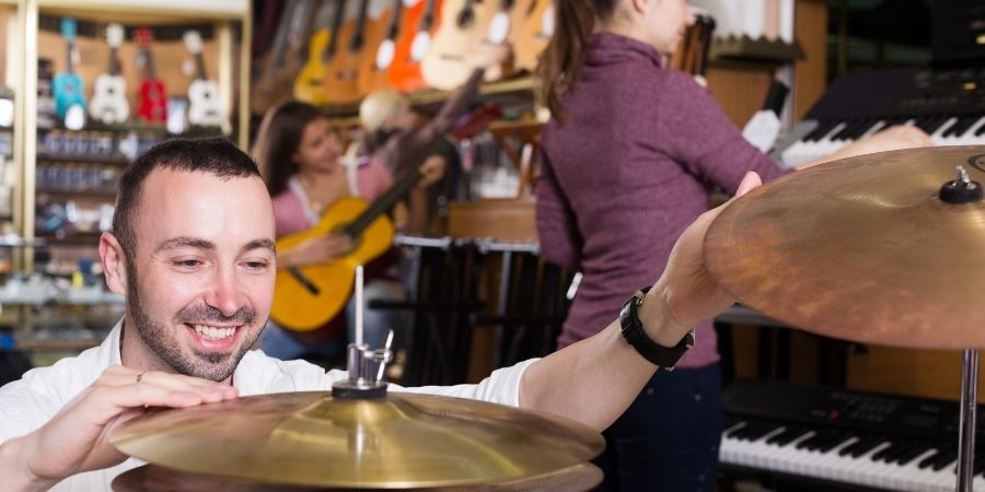 hombre platillo de batería musical en una tienda de instrumentos
