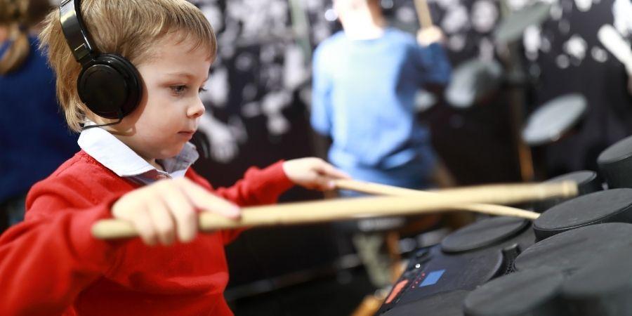 Niño con audífonos tocando batería digital